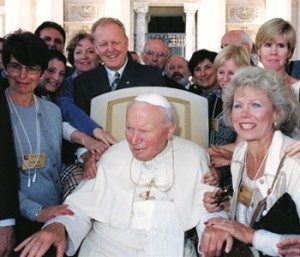 Nancy Gunderson (in white, beside the Pope) places her hand on St. John Paul II's hand, while Lynn and Michael Joseph (directly behind the Pope's chair) look on.