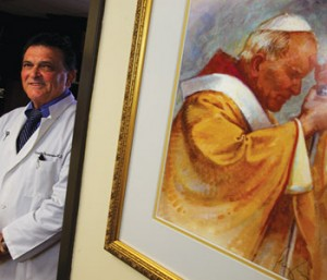 Dr. Vince Fortanasce poses with a portrait of St. John Paul II in his office in Arcadia, Calif.