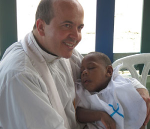 Fr. Marcel Taillon holds a newly baptized baby during a mission trip to the Dominican Republic