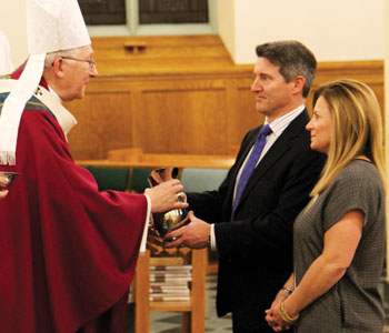 Bill and Paula Teed present the gifts to Archbishop Leonard Blair at the Dec. 10 chartering Mass