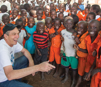 Orange Coast Legate Ralph Linzmeier reacts to the children in east-central Uganda during a mission trip last summer (Lou Metzger/Wells of Life photo)