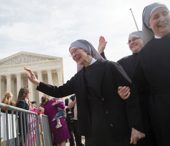 Little Sisters of the Poor wave to supporters at the U.S. Supreme Court on May 16