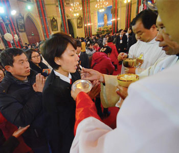 Catholics receive Holy Communion during Mass in Beijing
