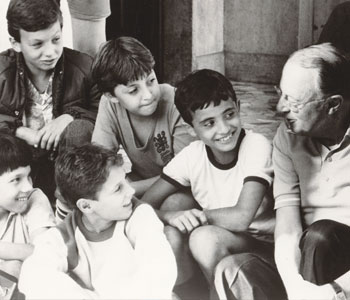 ACIL founder Monsignor Carroll-Abbing chats with children at Boys' Town in Rome during the 1980s